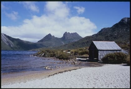 Hut near the edge of a lake with Cradle mountain in the background